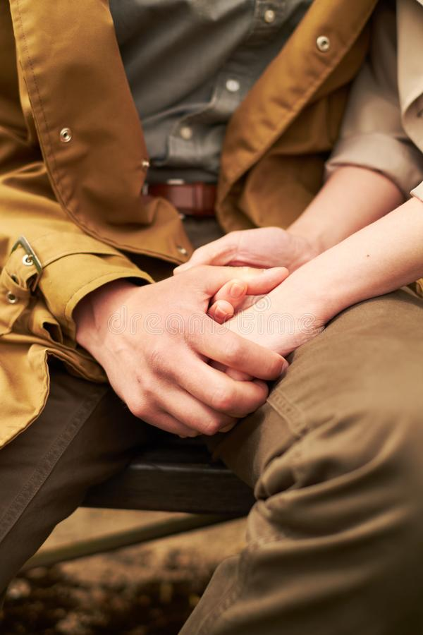 Руки и сердца совместно Конец-вверх любящих пар держа руки пока идущ outdoors стоковая фотография