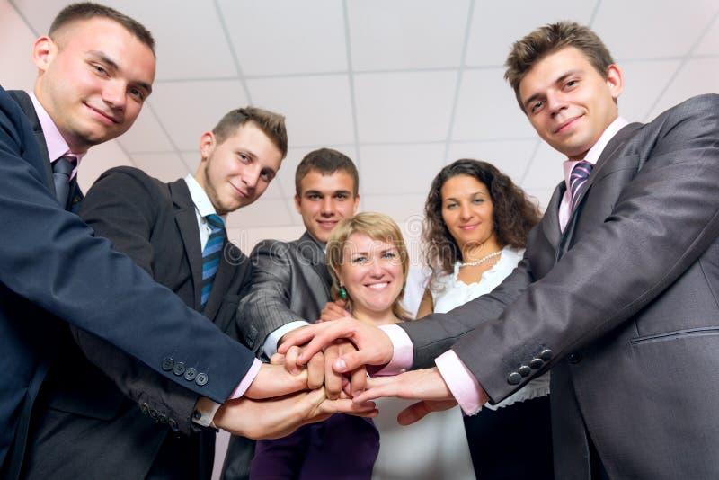 Руки и усмехаться счастливой команды дела соединяя стоковое изображение