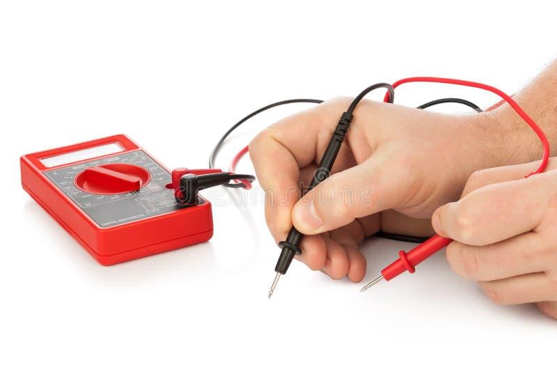 Руки и электрический вольтамперомметр стоковые изображения rf
