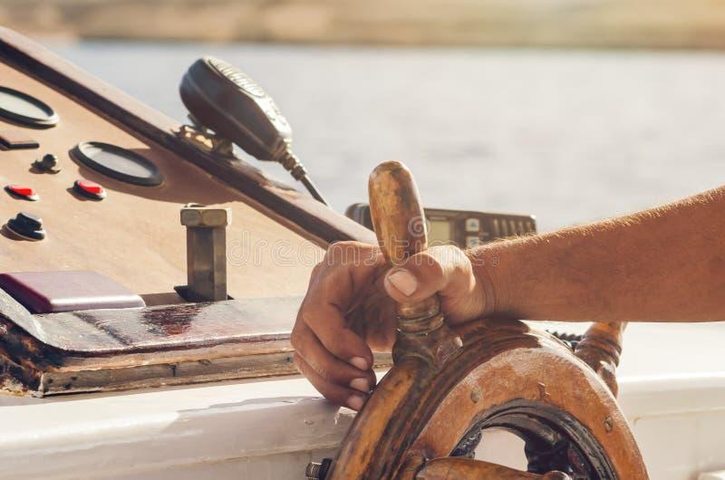 Руки капитана держа колесо на палубе корабля стоковое фото