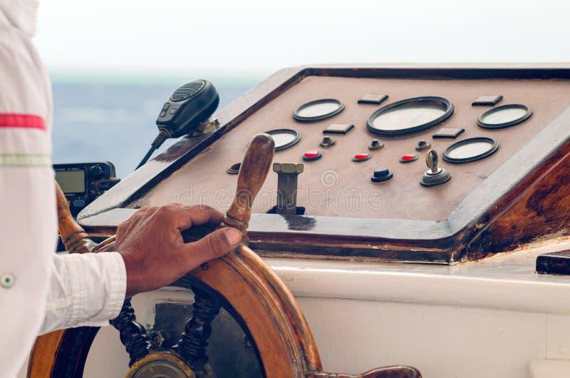 Руки капитана держа колесо на палубе корабля стоковое изображение rf