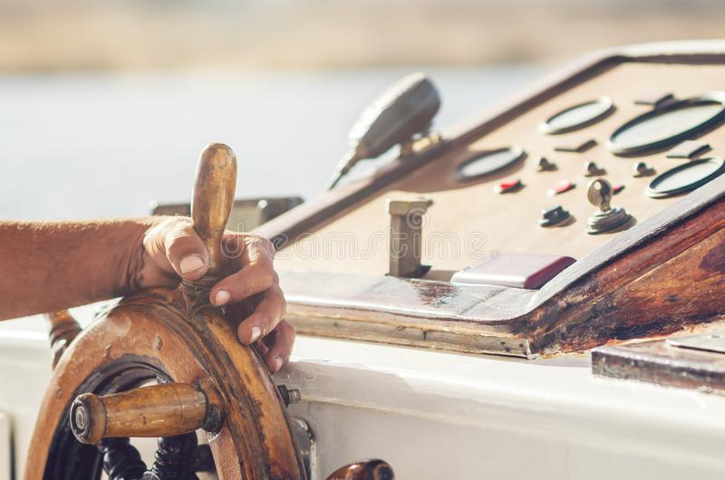 Руки капитана держа колесо на палубе корабля стоковое фото rf