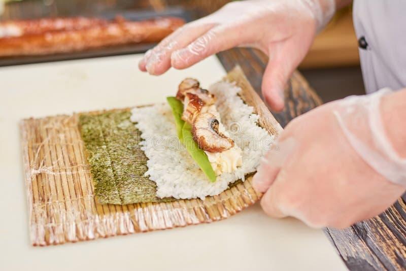 Руки кашевара делая японский крен суш стоковые изображения