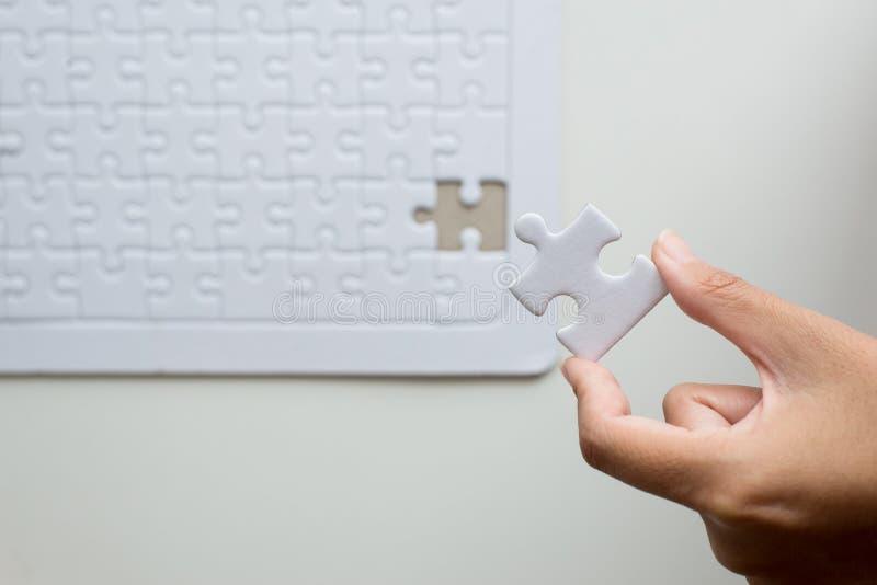 Руки кладя часть к белой мозаике, шаблону решения мозаики успеха, сыгранности дела партнерства концепции успешной стоковое фото rf
