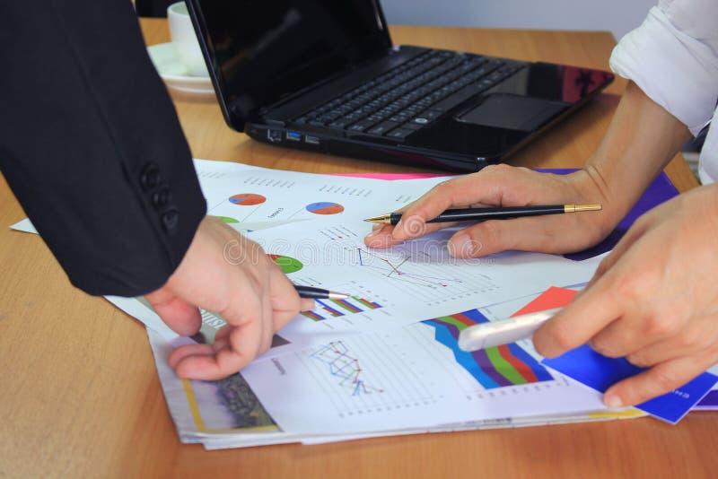Руки команды дела на работе с обсуждать диаграммы и базу данных диаграмм на таблице стоковое изображение