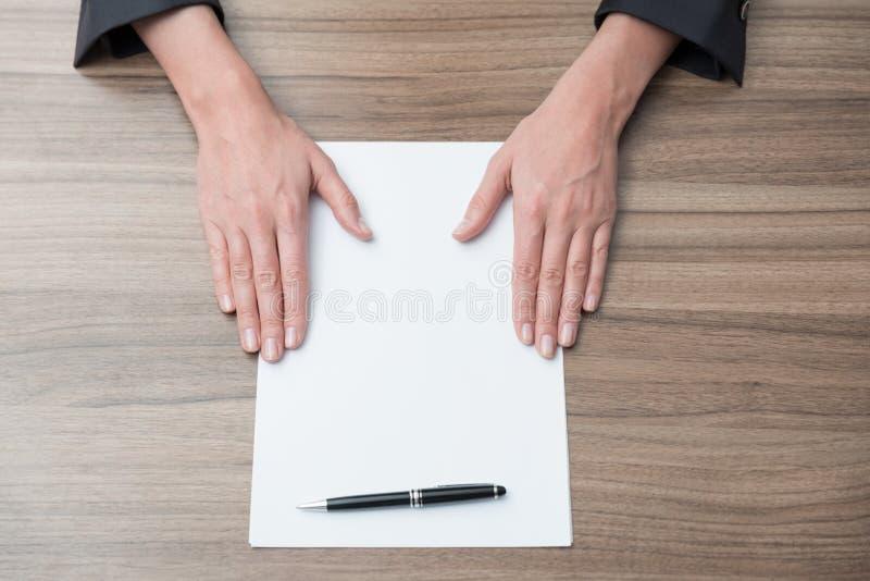 Руки коммерсантки на столе с чистым листом бумаги Законные переговоры контракта стоковые изображения