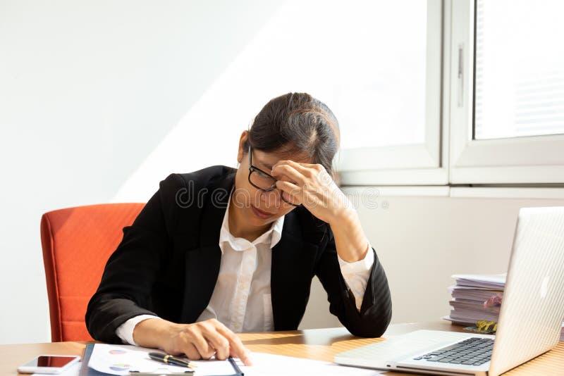 Руки коммерсантки отдыхая на голове с глазами близкими на рабочем столе в офисе стоковые изображения
