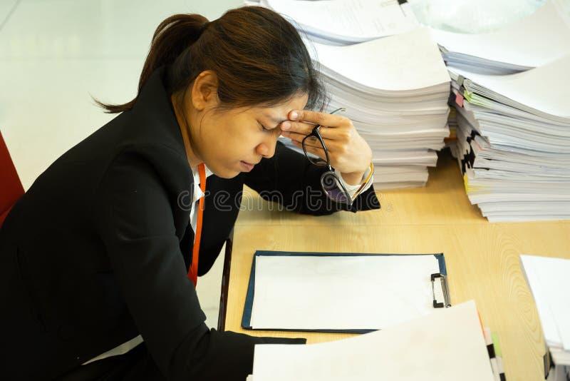Руки коммерсантки отдыхая на голове с глазами близкими на рабочем столе в офисе стоковые изображения rf