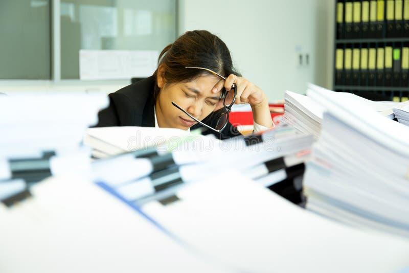 Руки коммерсантки отдыхая на голове с глазами близкими на рабочем столе в офисе стоковое изображение