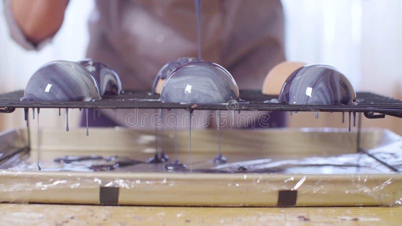 Руки кондитера лить теплую поливу зеркала на шариках замороженного мусса стоковое изображение rf