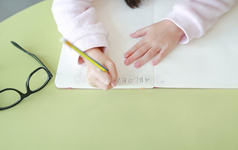 Руки конца-вверх маленького ребенка пишут ABC в книге или тетради с карандашем на таблице в классе против белой предпосылки стоковое фото rf