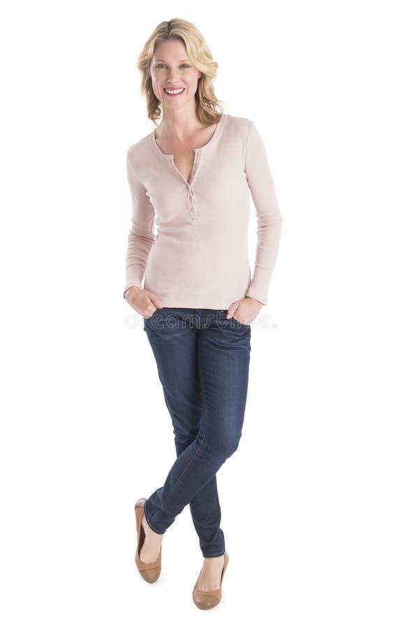 Руки красивой женщины стоящие в карманн над белой предпосылкой стоковое фото rf