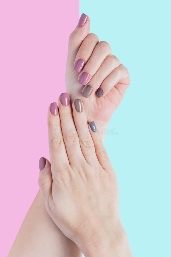 Руки красивой молодой женщины изолированные на пастельной розовой и голубой предпосылке Стильный ультрамодный женский маникюр с с стоковые фотографии rf