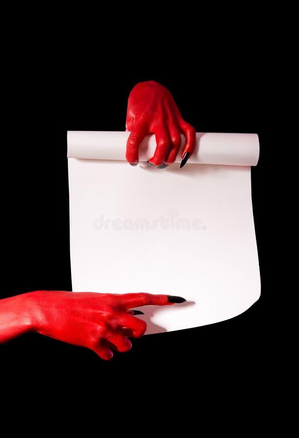 Руки красного дьявола при черные ногти держа бумажный перечень стоковое изображение rf