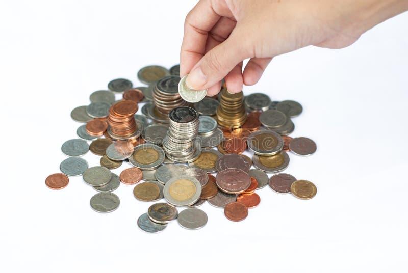 Руки кладя изолированные монетки на белую предпосылку стоковые изображения