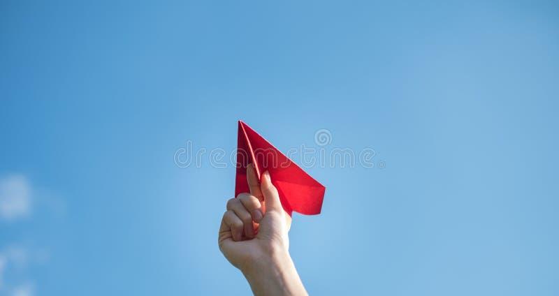 Руки людей держат красную бумажную ракету с яркой голубой предпосылкой стоковое изображение rf