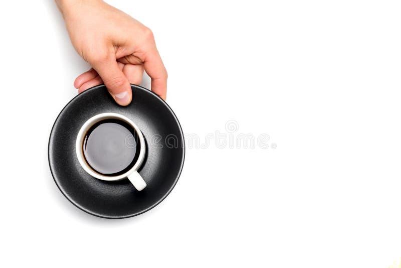 Руки людей держа черную чашку кофе на белой изолированной предпосылке, месте для текста стоковое изображение