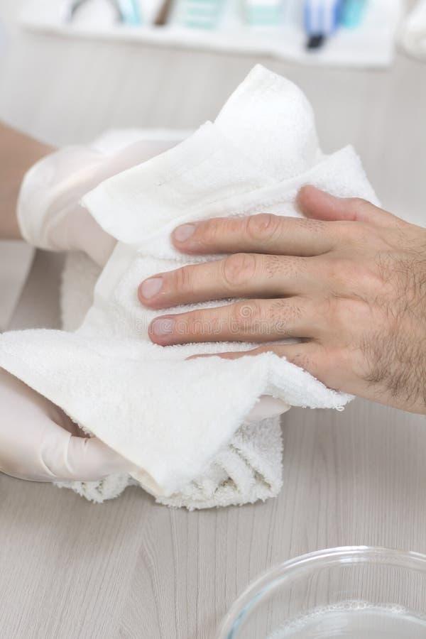 Руки людей обтерли с полотенцем руками beautician во время обработки маникюра Человек в салоне красоты стоковые фотографии rf