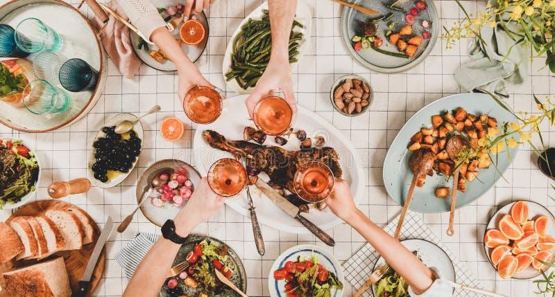 Руки людей clikning с рюмками над таблицей с закусками стоковое фото rf