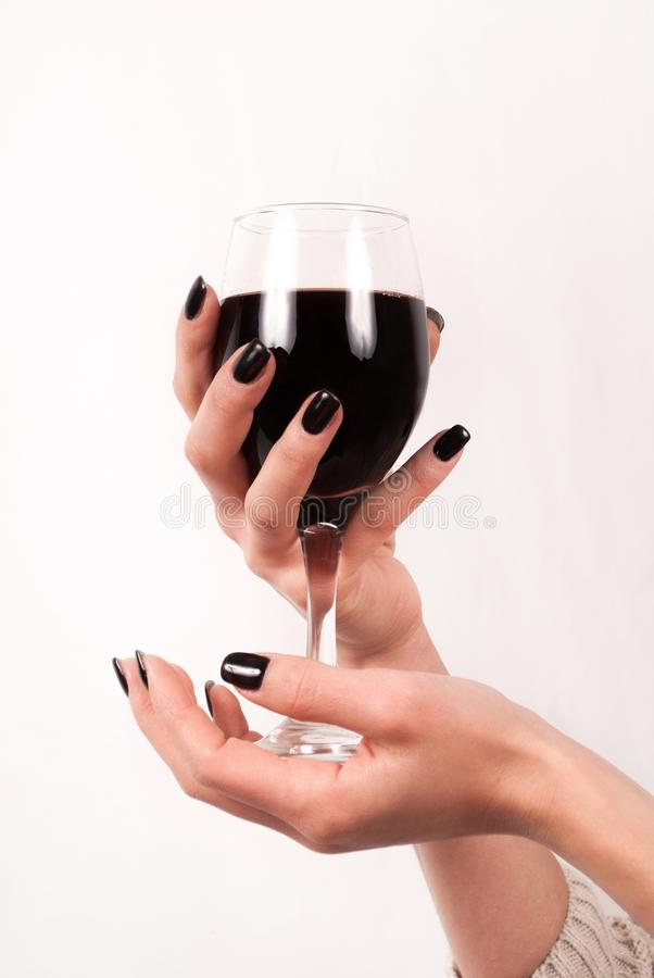 Руки маленькой девочки с черными ногтями держа стеклянными с красным вином,  концом вверх Стоковое Фото - изображение насчитывающей изолировано, перст:  104963350