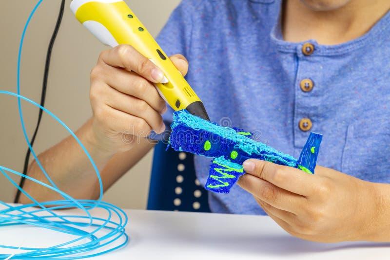 Руки мальчика создаваясь с объектом ручки печатания 3d новым стоковое фото