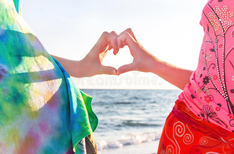 2 руки мальчика и девушки (подростков) в форме сердца стоковая фотография