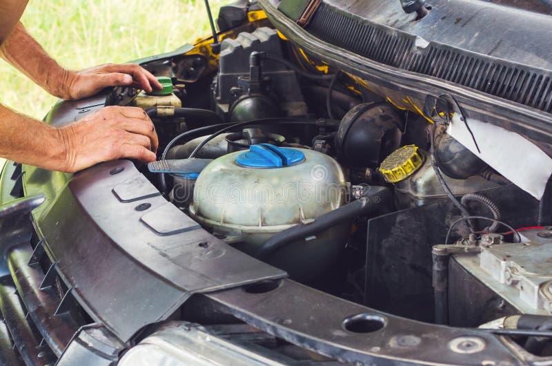 Руки механика выполняя проверку двигателя автомобиля стоковые фото