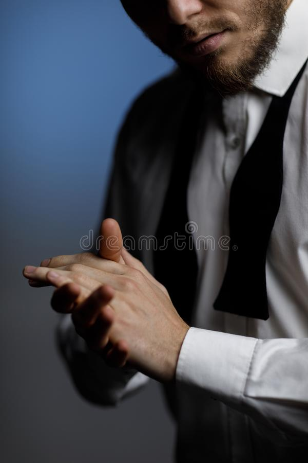Руки молодого бородатого человека в рубашке и развязанной бабочке стоковые фотографии rf
