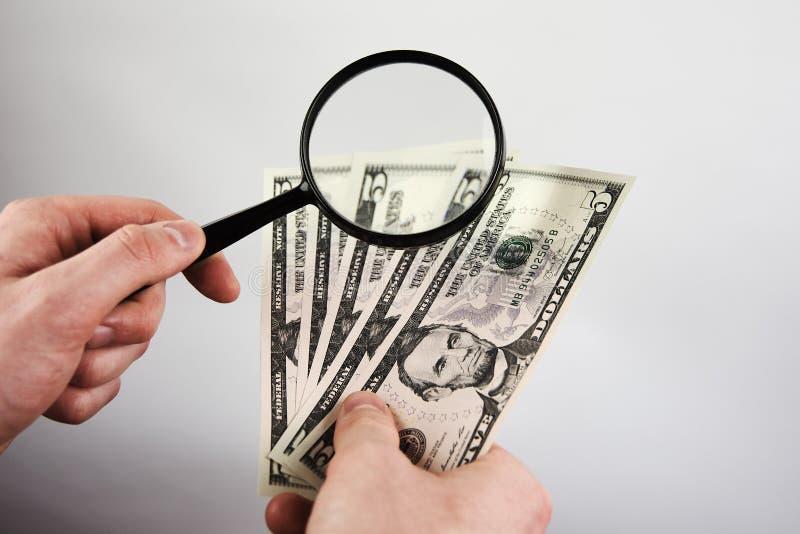 Руки молодого человека держа лупу и долларовые банкноты стоковые изображения rf
