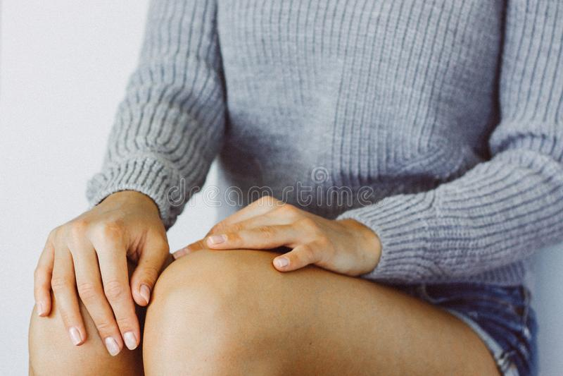 Руки молодой женщины на ее коленях, руки с ясным маникюром, молодой женщиной в одеждах непринужденного стиля стоковая фотография rf