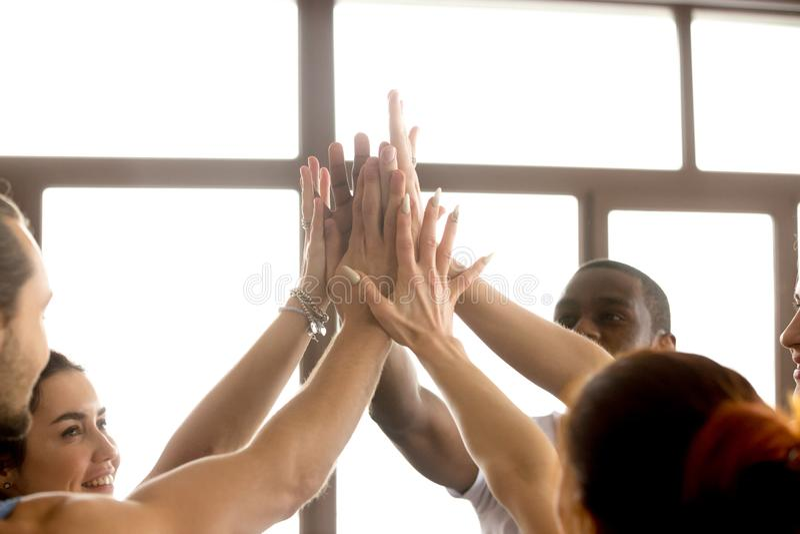 Руки мотивированной мульти-этнической команды соединяя совместно давая высокий f стоковое фото