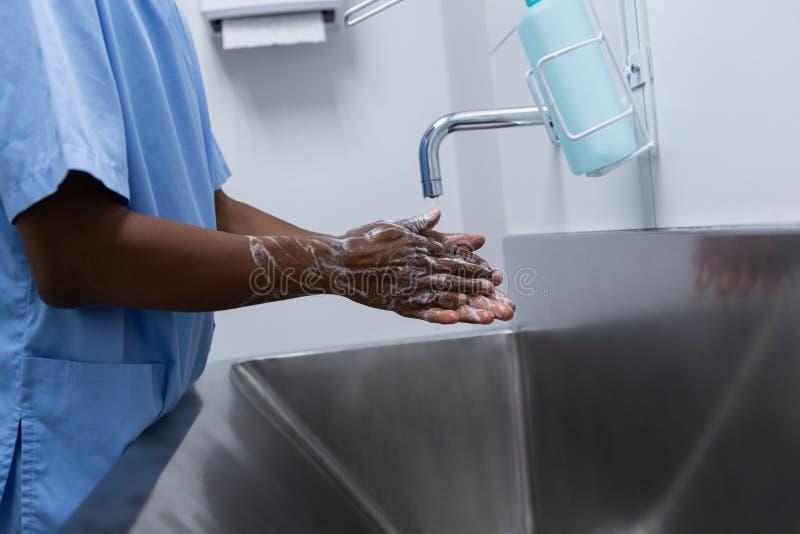 Руки мужского хирурга моя в раковине на больнице стоковое фото rf