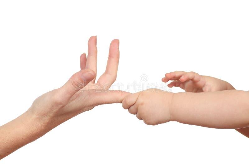 Руки младенца хватая ее перст матери стоковые изображения