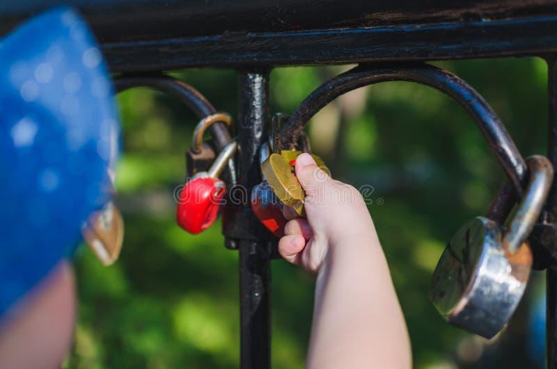 Руки небольшого владения ребенка замок любов прикрепленный к перилам моста стоковая фотография rf