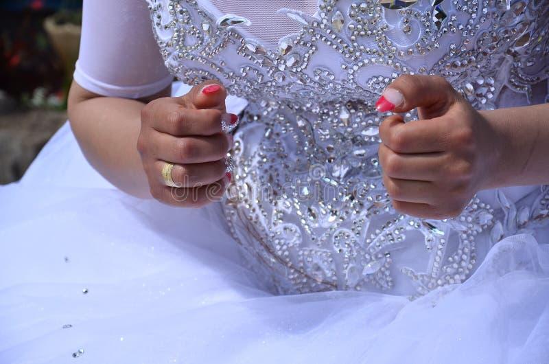 Руки невесты в белом платье с красным маникюром стоковая фотография rf