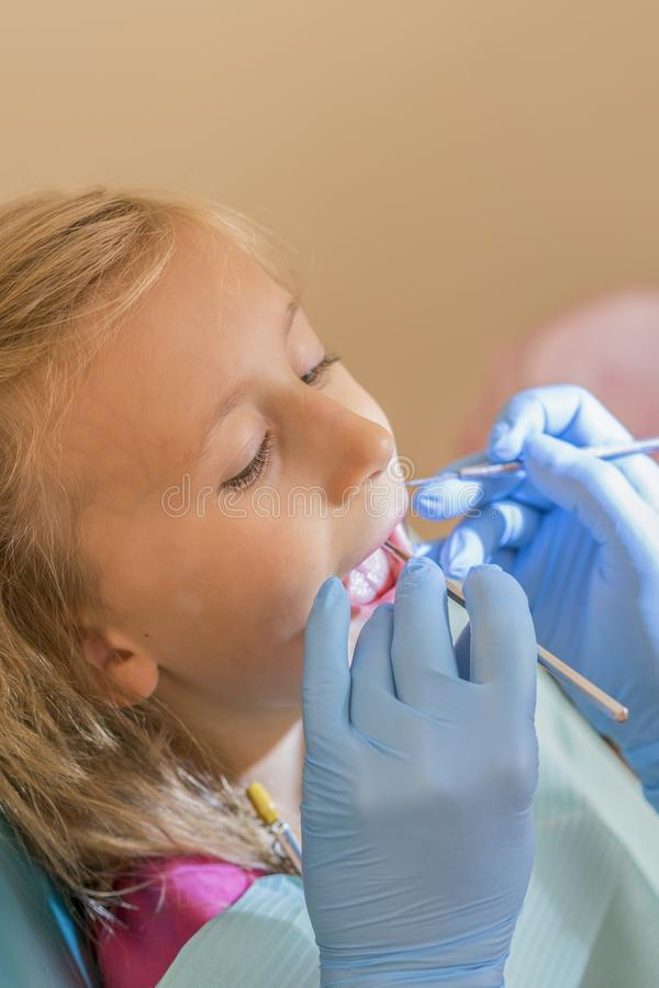 Руки непознаваемого педиатрического дантиста делая процедуру по рассмотрения для усмехаясь милой маленькой девочки сидя на стуле  стоковое изображение