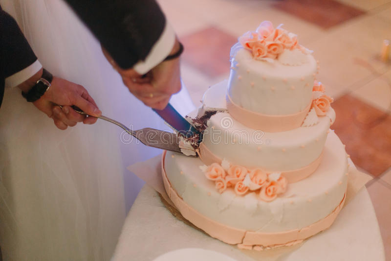 Руки новобрачных режут первую часть свадебного пирога Фото Конца-вверх стоковое фото rf