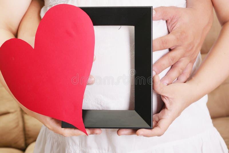 Руки обнимая беременную женщину belly при ее руки держа a стоковое фото rf