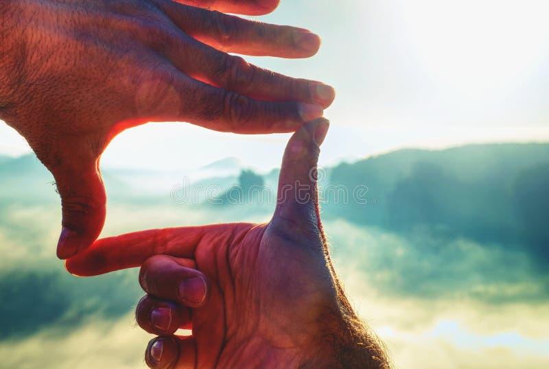 Руки обрамляя заход солнца взгляда дистантный излишек, винтажный фильтр стоковое фото rf