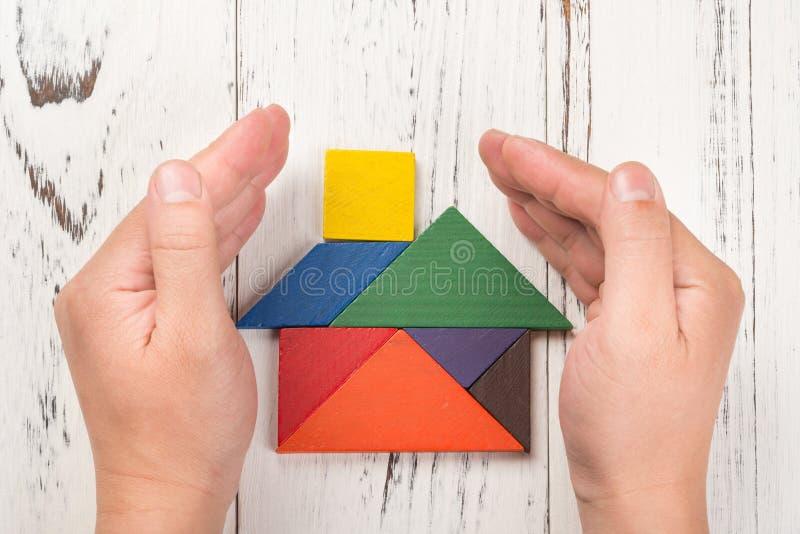 Руки окружают деревянный дом сделанный концепцией страхования жилья tangram стоковые фото