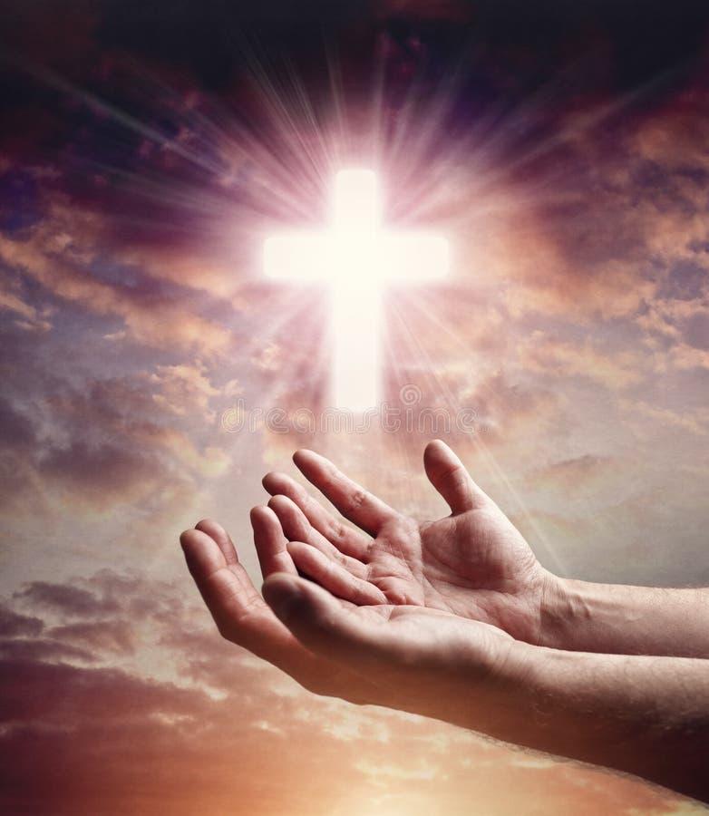 Руки достигая вне с крестом распятия в небе захода солнца стоковые изображения