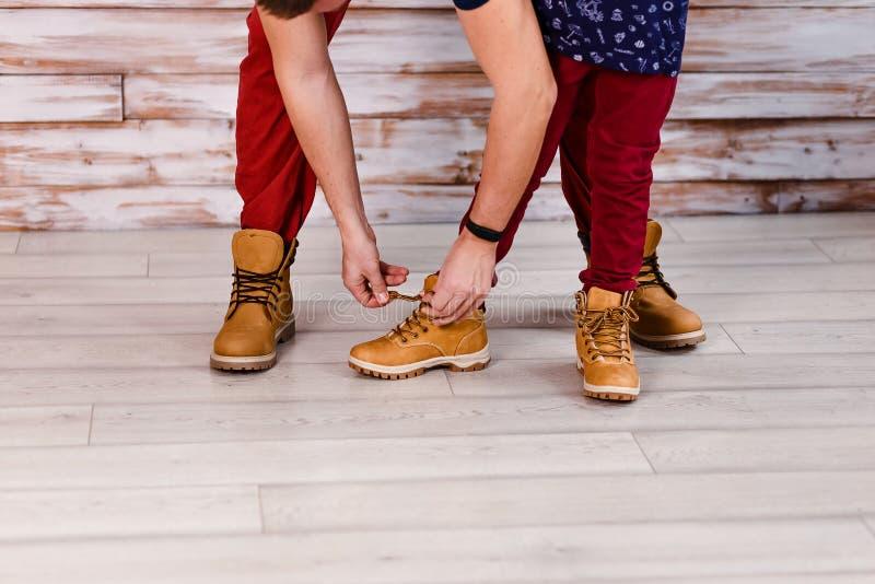 Руки отца связывают шнурки на ботинках ребенка закрывают стоковая фотография