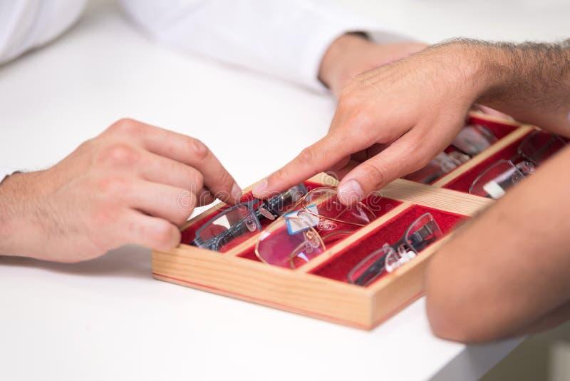 Руки офтальмолога закрывают вверх, показывающ поднос с различными стеклами к клиенту стоковые фото