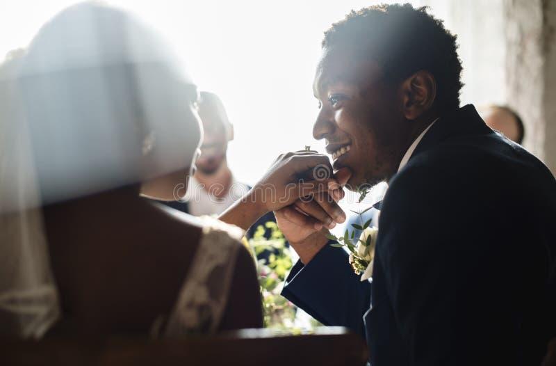 Руки пар африканского происхождения новобрачных целуя стоковое изображение rf