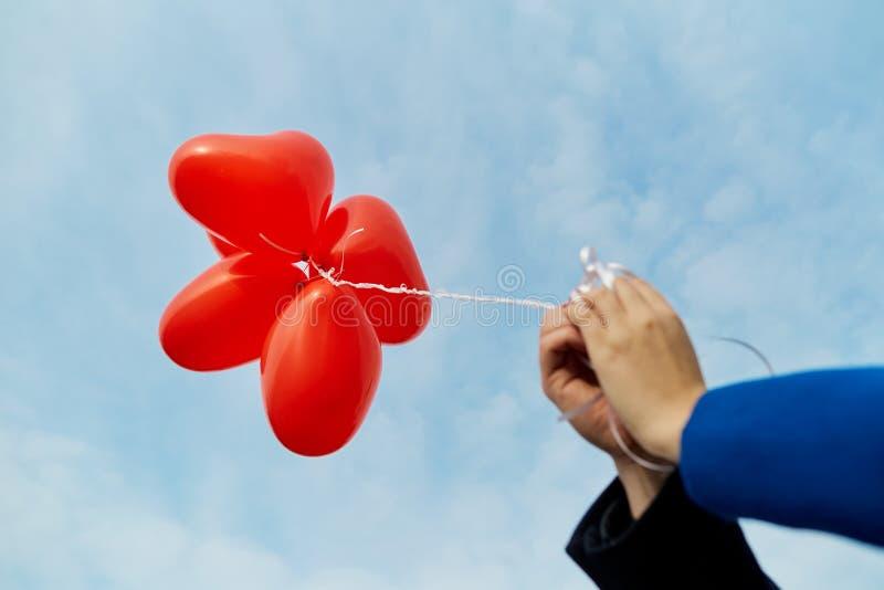 Руки пар держат баллоны в красном сердце стоковые фотографии rf