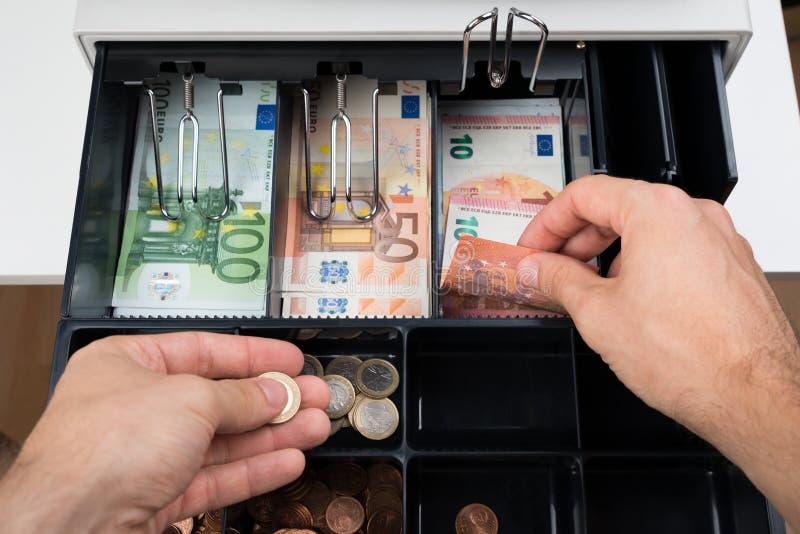 Руки персоны с деньгами над кассовым аппаратом стоковая фотография