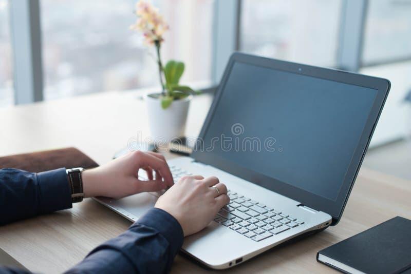 Руки печатая на клавиатуре компьтер-книжки Человек работает в офисе на его рабочем месте стоковое изображение
