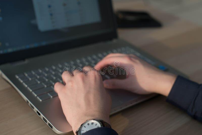 Руки печатая на клавиатуре компьтер-книжки Человек работая в рабочем месте стоковое фото