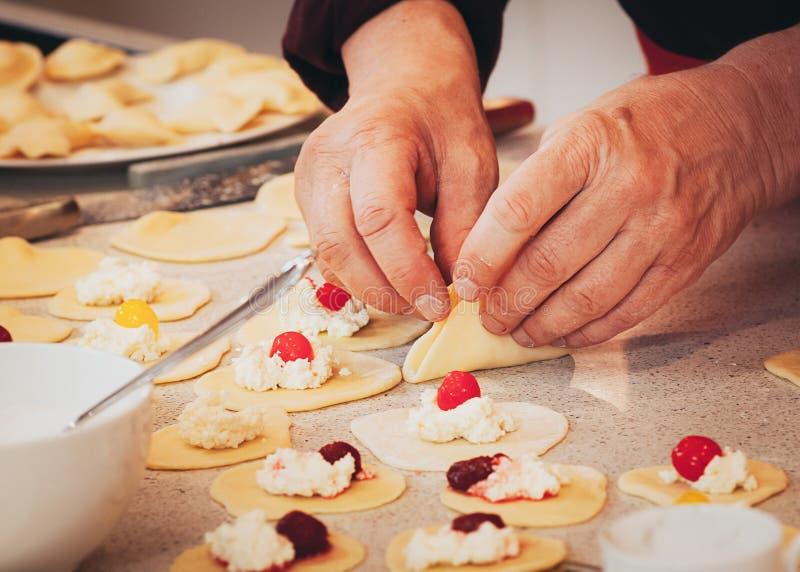 Руки подготавливая вареники сыра и вишни стоковое фото