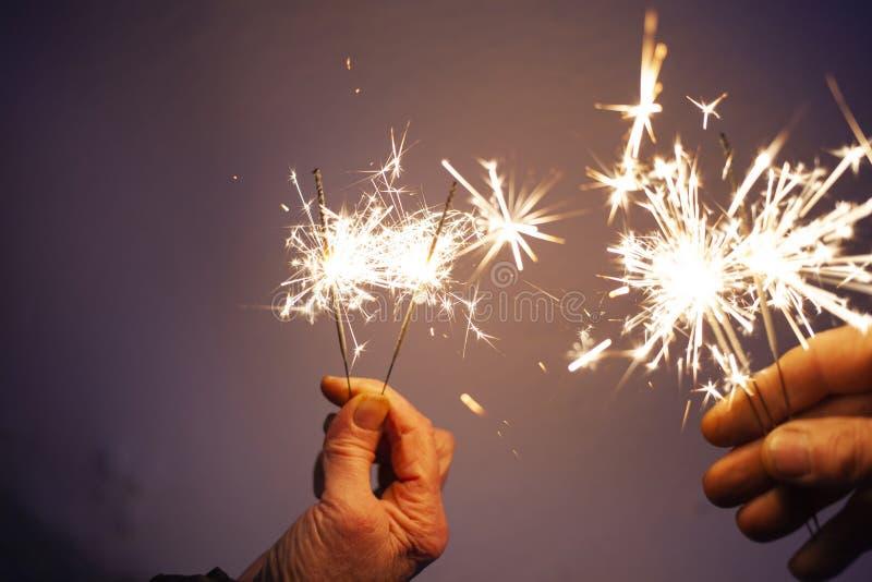 руки пожилого удерживания пар сверкнают празднующ Новый Год стоковая фотография